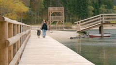 Red haird girl is walking over bridge by beautiful lake Stock Footage