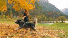 Red haird girl is running with her dog trugh autumn leaves in slow motion Stock Footage