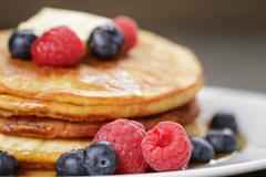 Stock Photo of Pancakes with raspberry, blueberry and maple syrup