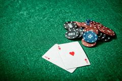 aces and chips on a green felt - stock photo