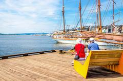 Pair of older people sitting on bench, Oslo Norway - stock photo