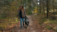 Girl walking trugh forest with big dog in autumn Stock Footage