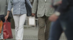 Happy mature couple with shopping bags walking through the city - stock footage