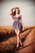 Beautiful girl in dress walking on the trai atl field Stock Photos