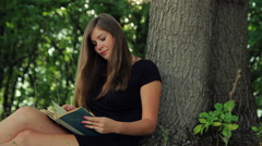Beautiful girl in a dress sits in a park under a tree reading a book in the sun Stock Footage
