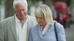 4K Happy smiling mature couple looking at map & mobile phone in the city - stock footage
