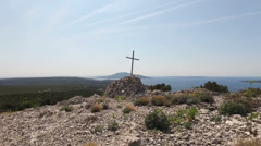 Aerial - Christian cross on top of seaside mountain - stock footage