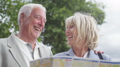 4K Happy smiling mature couple looking at map in the city - stock footage