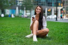 Beutiful happy woman sitting on green grass at city park and using smartphone - stock photo