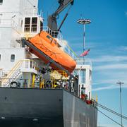 Orange free-fall life boat for emergency crew evacuation installed on cargo s Stock Photos