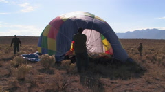Passengers assist in deflating a hot air balloon Stock Footage