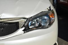 Stock Photo of Broken front headlight on white car.
