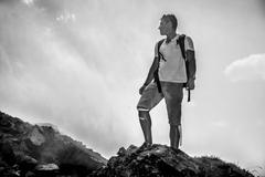 Black and white photo of travel man standing on the rock on the cloud Stock Photos