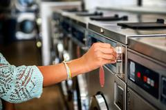 Photo of woman hand put quarter coin on the laundry machine in public laundry Kuvituskuvat