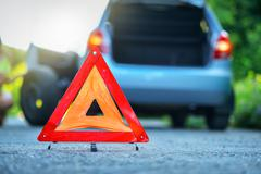 Changing the tire on a broken down car on a road with red warning triangle Stock Photos