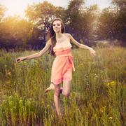 Beauty Girl Outdoors enjoying nature and runngin on the meadow. - stock photo