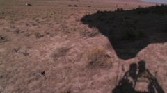 A hot air balloon travel just above the valley floor showing the balloons shadow Stock Footage