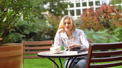Girl sitting in the outdoor cafe and looking morose Stock Footage