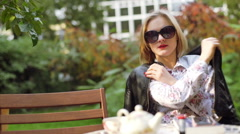 Irritated woman waiting for someone in the outdoor cafe - stock footage