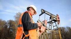 Engineer  with tablet computer inspects the oil pumping unit. Stock Footage