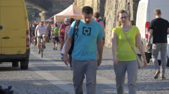 Walking and riding bikes on a cobblestone street in Prague Stock Footage