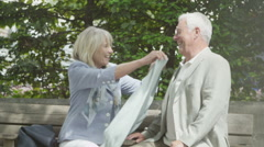 Happy mature couple with shopping bags, looking at their purchases outdoors - stock footage