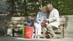 4K Happy mature couple with shopping bags, looking at computer tablet outdoors - stock footage