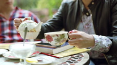 Girl pouring tea from teapot to cup while relaxing in the outdoor cafe Stock Footage