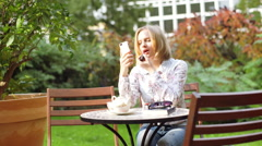 Girl sitting in the outdoor cafe and improving her makeup Stock Footage