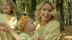 Young happy mother and her children with maple in autumn park Stock Footage