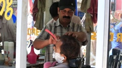Indian barber working with a client in street. Dharamsala, India Stock Footage
