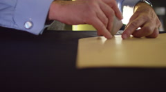 4K Close up on hands of a tailor working in his shop, drawing template on fabric - stock footage