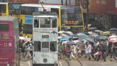 Traffic in Hong Kong with double decker tram and people crossing street - stock footage