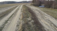 Aerial view of byroad throught field in country side, sand dirty road, near icy Stock Footage