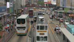 Traffic in Hong Kong with double-decker buses, trams and people crossing street - stock footage