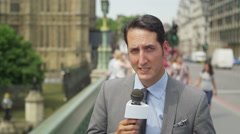 Stock Video Footage of 4K News reporter doing live piece to camera outside London Houses of Parliament