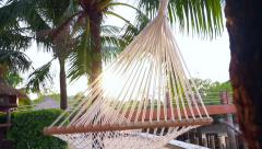 Hammock hung between palm trees on a tropical beach in morning sunlight Stock Footage