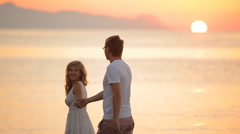 Beautiful couple walking along the shore of the Aegean Sea Stock Footage