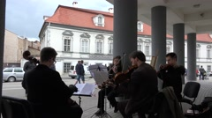 String instrument quartet play on theater square with column. 4K Stock Footage