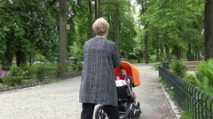 Stock Video Footage of Old woman grandmother push stroller on park path. 4K