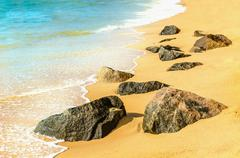 Turquoise waves of water flowing stones on beach Stock Photos