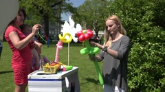 Young creative girl twist bunny or flower shape from balloons. 4K Stock Footage