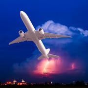 Commercial airplane flying with clouds and thunderstorm background - stock photo