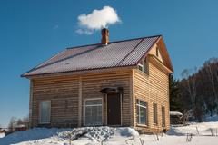 Log house in winter with a blue sky - stock photo