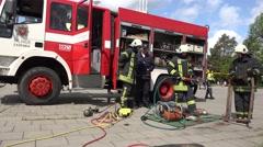 Firefighters demonstrate hydraulic equipment near fireman truck. 4K Arkistovideo