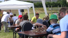 Children with parents play chess in free outdoor tournament. 4K Stock Footage