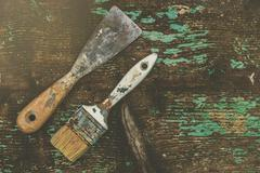 Old paintbrush and spatula on rustic wooden board Stock Photos
