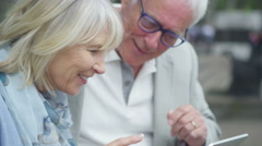 4K Happy mature couple using technology in the city Stock Footage