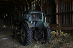 Blue farm tractor with tractor driver, under roof of hayloft. Stock Photos