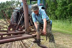 Farmer tractor-driver, repairing old tractor hay rake in mown meadow. Stock Photos